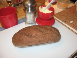 One loaf of pumpernickel bread on cutting board with butter-bell