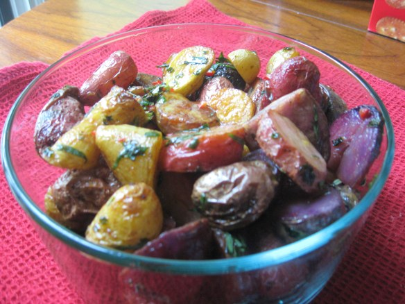 roasted potatoes, with herbs and chili peppers in serving dish.